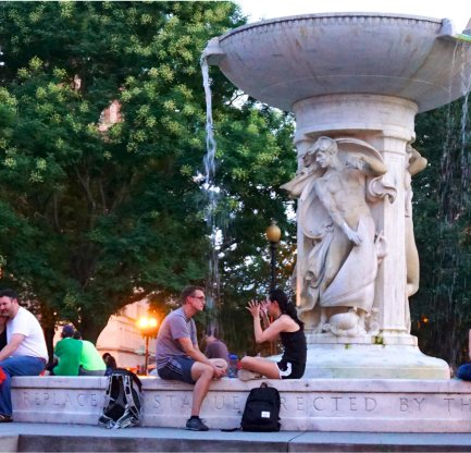 A couple chat below the statue and fountain at Dupont Circle