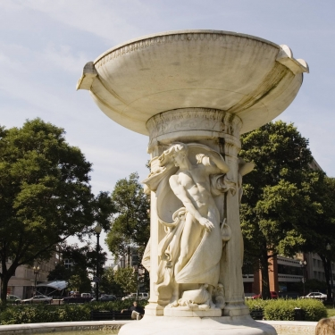 A statue of a woman or man in the middle of a circular fountain