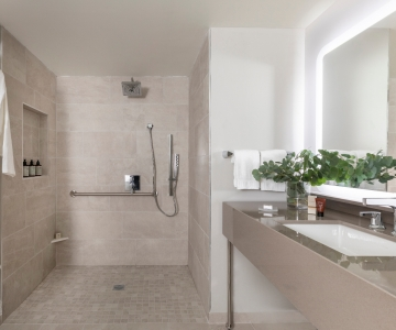 An interior view of the modern bathroom found in a Madera Double Queen ADA
