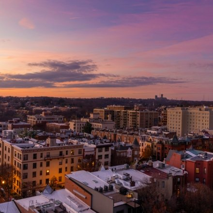 A view of the sunset and purple sky above Washington, DC buildings