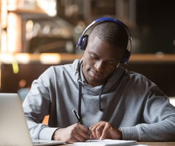 A student studying at the Howard University library with a laptop and headphones on