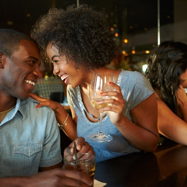 A woman and a man laughing and enjoying a drink