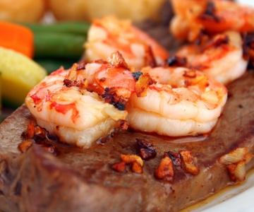 Shrimp served on top of a juicy steak