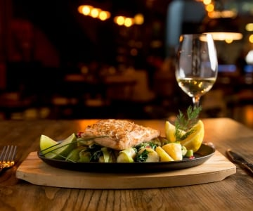 A salmon served on top of fresh vegetables paired with a glass of white wine