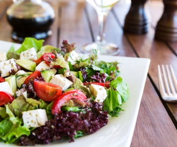 A colorful salad with greens, red peppers and feta cheese