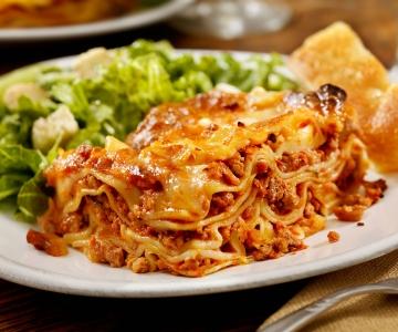 A big lasagna served with a Caesar salad