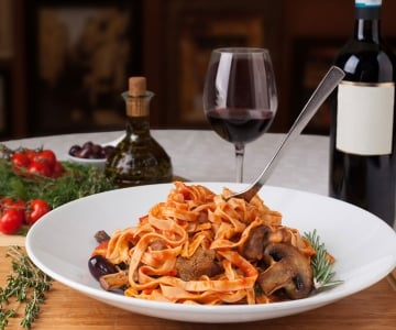 A spaghetti dish with a glass full of red wine and wine bottle