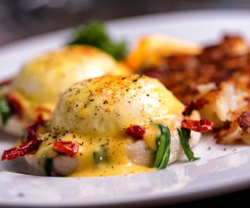 An eggs benedict served with hash browns
