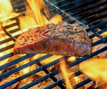 A piece of meat or fish on a fire blazing grill