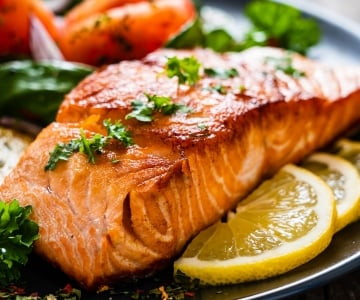A salmon dinner served with fresh herbs and lemon slices